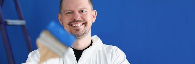 Reparador sorridente segurando um pincel de construção com tinta azul