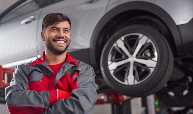 Reparador sorrindo sorrindo perto de um automóvel suspenso na oficina
