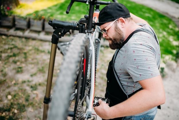 Reparador trabalha com roda de bicicleta, oficina de bicicletas