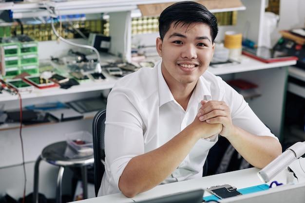 Reparador, trabalhando na loja de reparo do smartphone