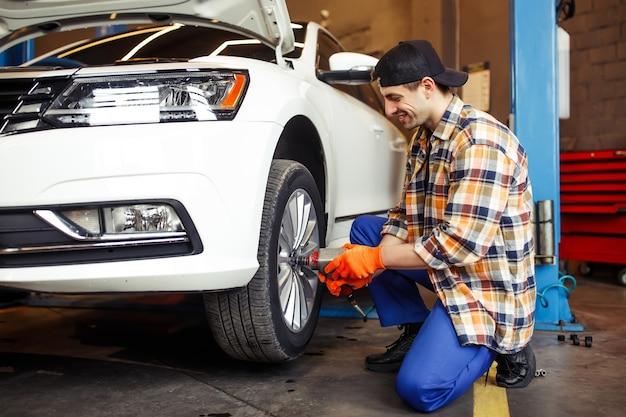 Reparador trocando a roda do carro usando uma chave pneumática na garagem