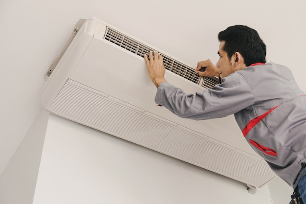 Reparadores de ar condicionado estão verificando e reparar o ar pendurado na parede.