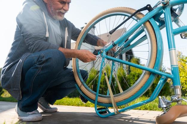 Reparando bicicleta. homem maduro barbudo vestindo jeans e jaqueta esporte azul escura consertando sua bicicleta azul