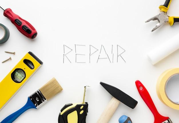 Reparar a palavra escrita com as unhas cercadas por ferramentas