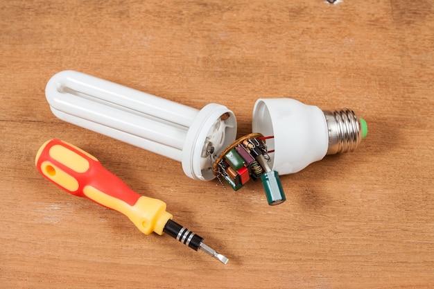 Reparar lâmpadas de poupança de energia na mesa de madeira.