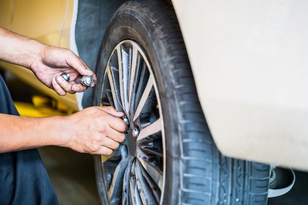Repare as mãos do mecânico durante o trabalho de manutenção para afrouxar a porca da roda, trocando o pneu do carro, consertando peças do veículo da roda do carro na garagem