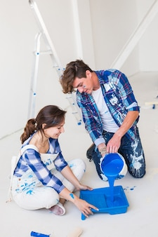 Reparo, cor, conceito de pessoas - casal vai pintar a parede, eles estão preparando a cor.