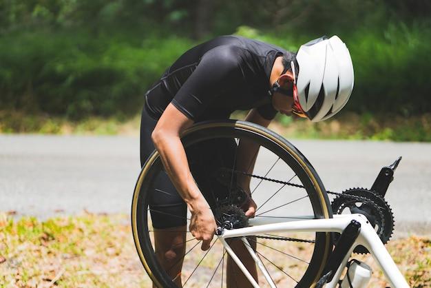 Reparo da bicicleta do ciclista na estrada, ele vazou pneus.