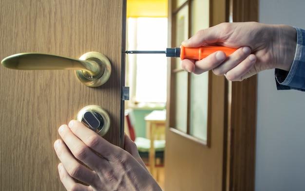 Reparo da maçaneta da porta. montando a fechadura na porta de madeira.