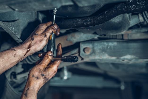 Reparo da parte inferior do carro em serviço, detalhe das mãos. copie o espaço