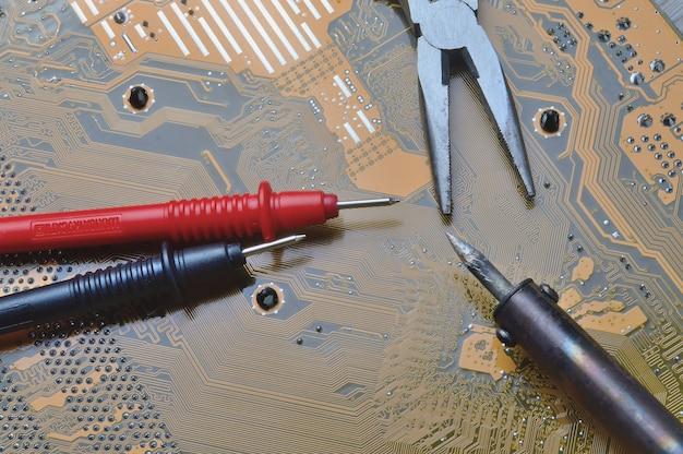 Reparo da placa-mãe do computador. ferro de soldar e alicate sobre o microcircuito.