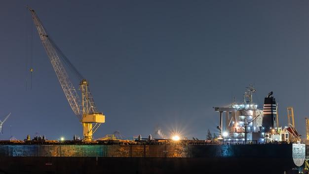 Reparo de navio de óleo de recipiente no estaleiro à noite. pode usar para transporte ou conceito de transporte.