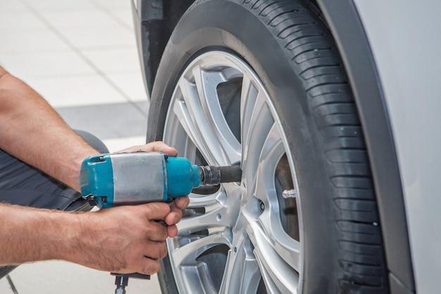Reparo do carro: close up da substituiço da roda. mecânico aparafusar ou desenroscando a roda de carro na garagem de serviço de carro