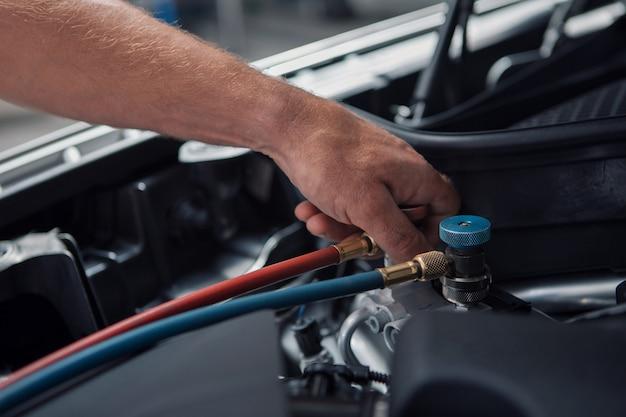 Reparo do carro e conceito de limpeza - close-up do motor de carro, limpando as peças sob o capô