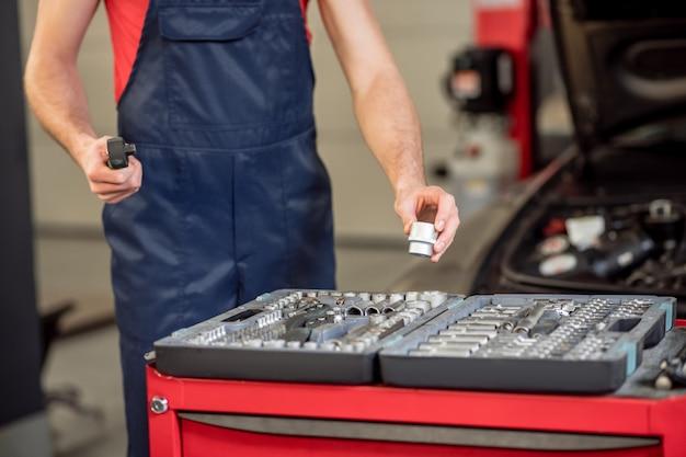 Reparo do carro. mãos de mecânico de automóveis em macacão azul com peças de reposição perto da caixa aberta com ferramenta e carro na oficina