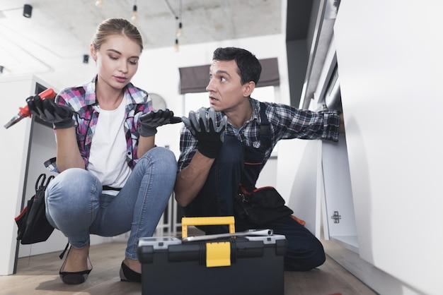 Reparo do encanador do homem e da mulher na cozinha na cozinha.