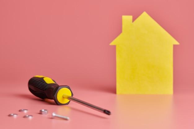 Reparo em casa e conceito redecorado. renovação de casas. parafusos e figura em forma de casa amarela em fundo rosa.