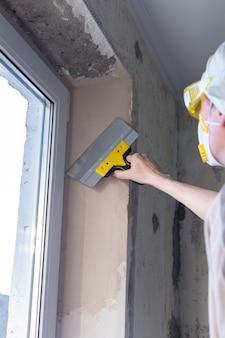 Reparo em um apartamento, cimentando aberturas de janelas, um construtor nivela a massa com uma espátula