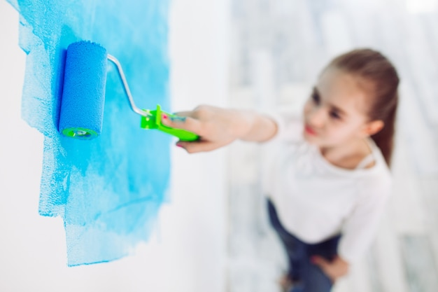 Reparo no apartamento. menina criança feliz pinta a parede com tinta azul