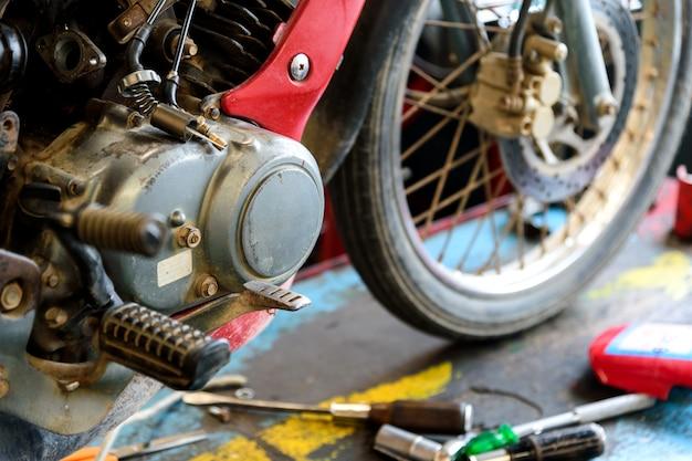 Reparo velho do motor da motocicleta com macio-foco e sobre a luz no fundo