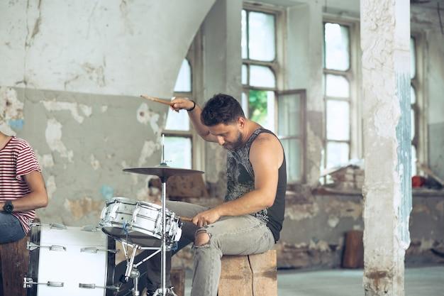 Repetição de banda de rock. baixista, guitarrista e baterista no loft. música rock e conceito de jam session. paixão pela música e conceitos de cultura jovem