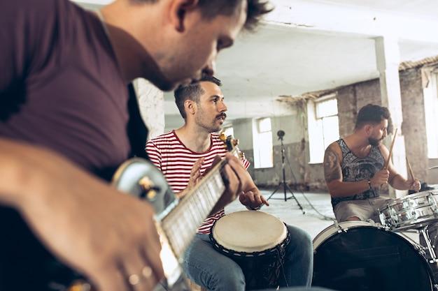 Repetição de banda de rock, baixista, guitarrista e baterista no loft