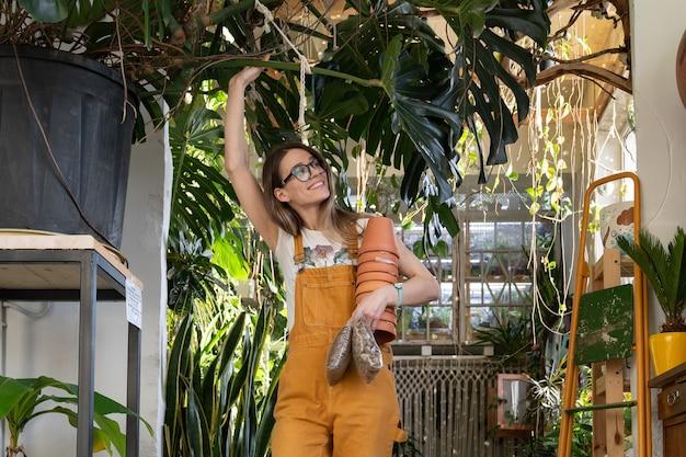 Replante de plantas de casa de florista feminina com drenagem de vaso