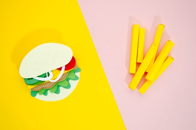 Réplicas de hambúrguer e batatas fritas em fundo colorido