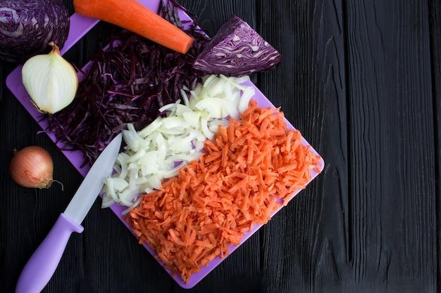 Repolho azul fresco picado, cebola e cenoura na tábua violeta sobre o fundo preto de madeira. vista superior. copie o espaço.