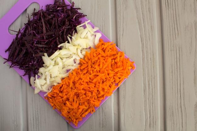 Repolho azul fresco picado, cebola e cenoura numa tábua violeta no fundo cinza de madeira. vista superior. copie o espaço.