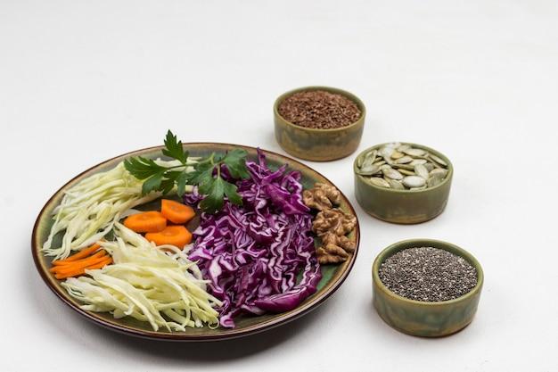 Repolho branco e roxo fatiado no prato. semente de linhaça, sementes de abóbora, chia preta em caixas. nutrição equilibrada. copie o espaço