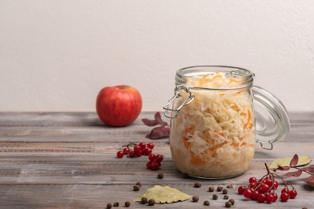Repolho caseiro enlatado com cranberries e maçã em uma jarra com tampas abertas com folhas de louro em uma mesa de madeira. fechar-se. copie o espaço