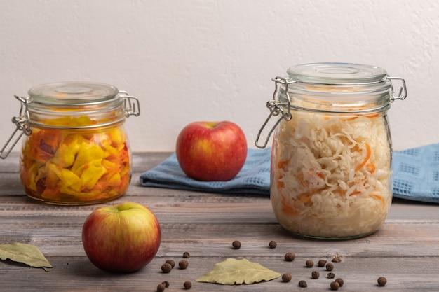 Repolho caseiro enlatado com maçãs em dois potes com folhas de louro em uma mesa de madeira. fechar-se. copie o espaço