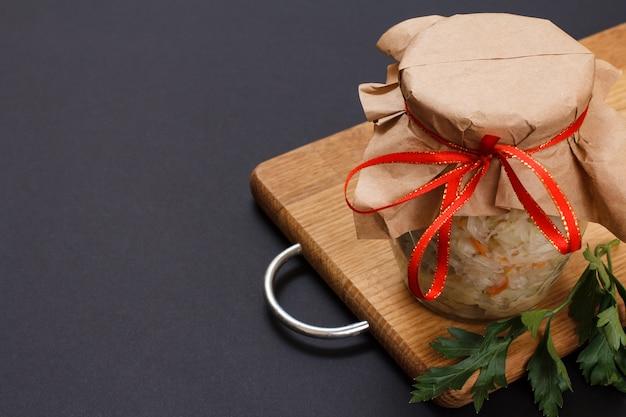 Repolho fermentado caseiro com cenoura em frasco de vidro na tábua de madeira e fundo preto. salada vegan. o prato é rico em vitamina u. comida excelente para uma boa saúde. vista do topo.