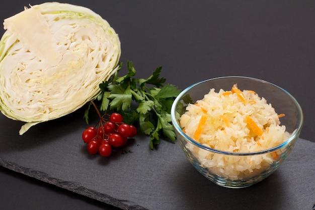 Repolho fermentado caseiro com cenoura em uma tigela de vidro. cabeça fresca de repolho e cluster de viburnum no fundo. salada vegan. o prato é rico em vitamina u. comida excelente para uma boa saúde.