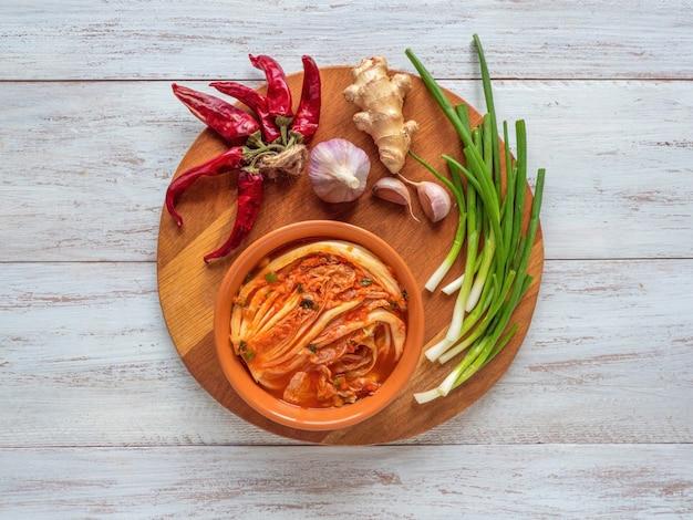 Repolho kimchi em uma tigela na mesa de madeira, vista superior.