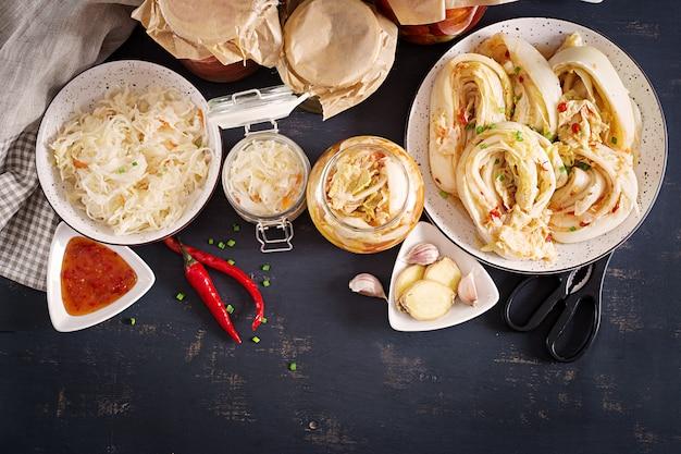 Repolho kimchi, tomate marinado, frascos de vidro azedo chucrute sobre a mesa da cozinha rústica.