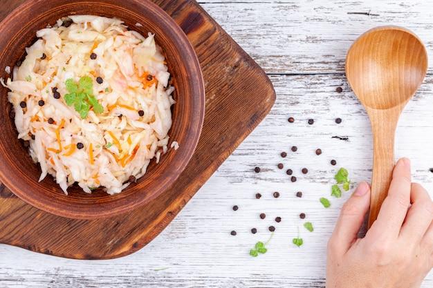 Repolho marinado caseiro, chucrute azedo em uma tigela de madeira na mesa da cozinha