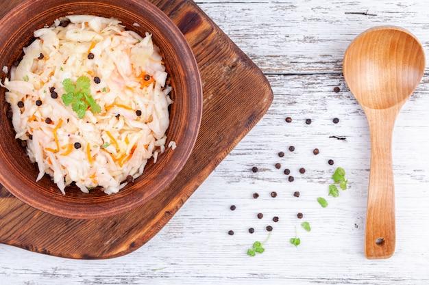 Repolho marinado caseiro, chucrute azedo na tigela de madeira mesa de cozinha