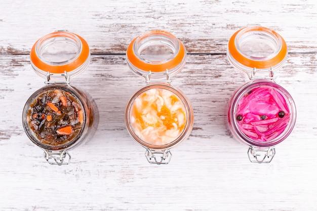 Repolho marinado caseiro kimchi, couve do mar, chucrute azedo em frascos de vidro abertos