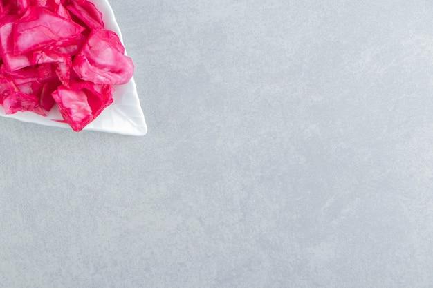 Repolho roxo colhido fatiado em uma travessa na superfície de mármore