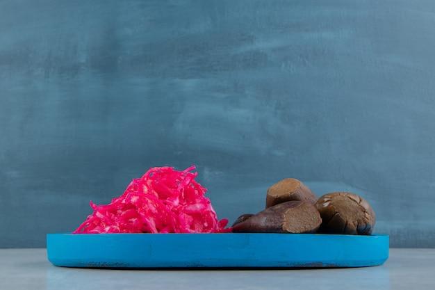 Repolho roxo em conserva e berinjela em um prato de madeira