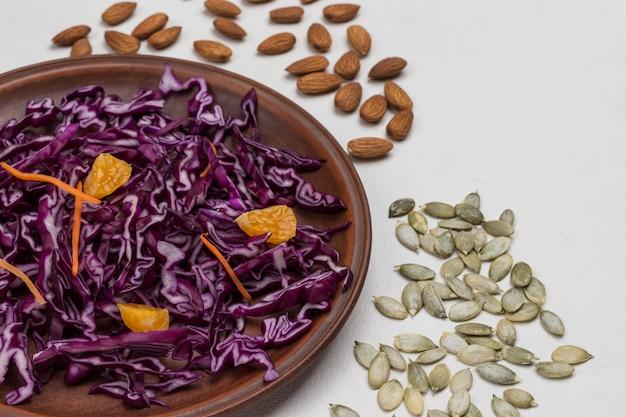 Repolho roxo fatiado. sementes de amêndoa e abóbora. comida vegana. comer limpo. vista do topo