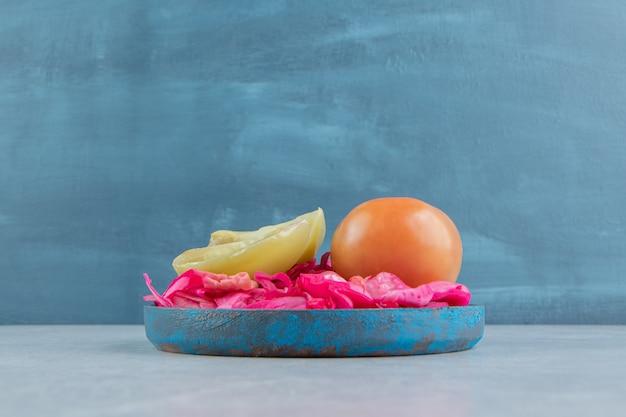 Repolho roxo fermentado, tomates inteiros e fatiados em um prato de madeira