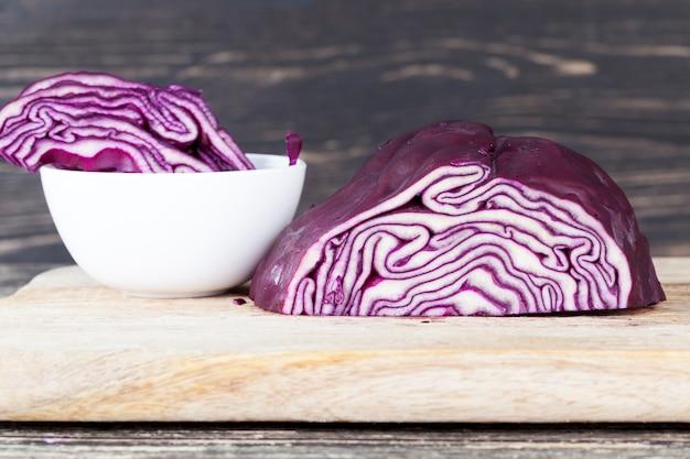 Repolho roxo picado em uma tábua de madeira durante o preparo da salada