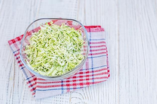Repolho verde em uma tigela de vidro. salada. fundo branco.