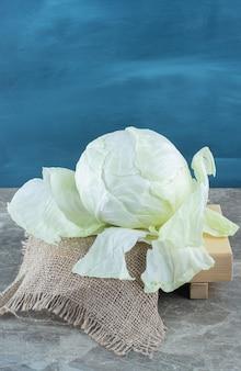 Repolho verde na placa de madeira, no tripé, na mesa de mármore.