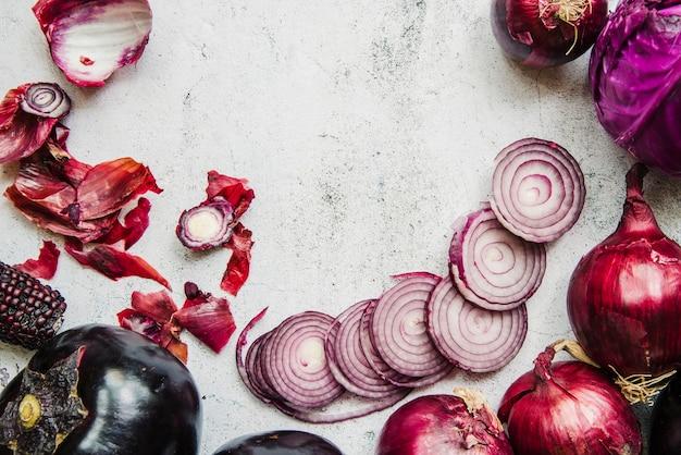 Repolho vermelho; cebolas; beringela e espiga de milho no pano de fundo branco texturizado