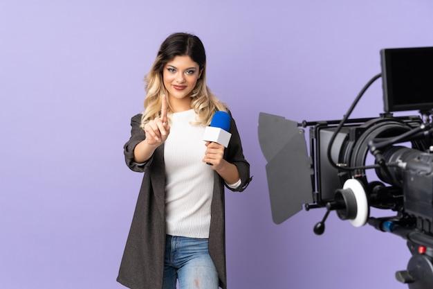 Repórter adolescente menina segurando um microfone e reportando notícias na parede roxa mostrando e levantando um dedo