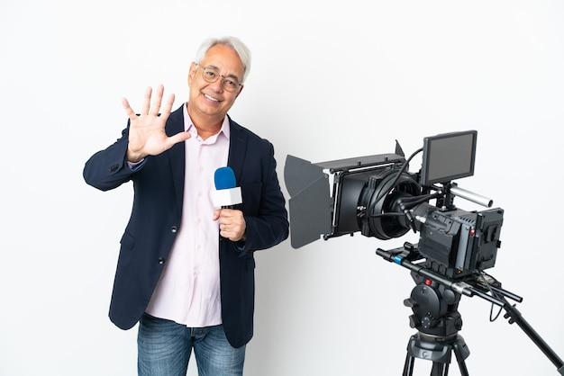 Repórter brasileiro de meia-idade segurando um microfone e relatando notícias isoladas contando cinco com os dedos